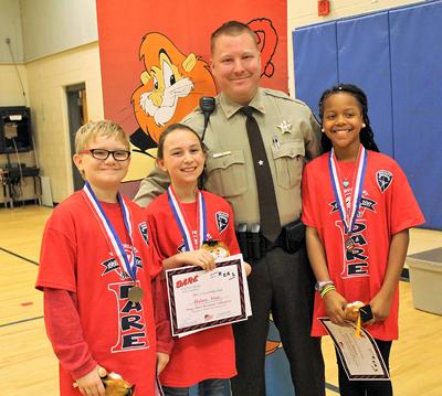 Dallas Elementary D.A.R.E. essay winners with Deputy Crowe. L-R, Mason Hembree, Chelsea Knox, Deputy Crowe, and Cadence Edmond