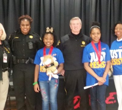 Deputy Arlene Sharpe, DARE Coordinator/Director, DARE Instructor Deputy Cynnamon Timmons D.A.R.E. Essay Winner with Daren, Ceigan Carter, Richland County Sheriff Leon Lott,  Amiyah Jackson, and Principal Mrs. Kezia Myers.